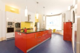 Modern Gloss Kitchen to listed family home with red and white units and blue vinyl floor