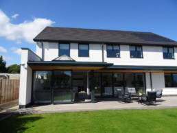 Rear Elevation of Modern Dwelling in Yorkshire with in-line Photovolatic panels to interlocking concrete tile roof and white reder walls